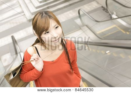 Smile shopping woman walk at escalate in Xinyi district, the business and commercial center in Taipei, Taiwan, Asia.
