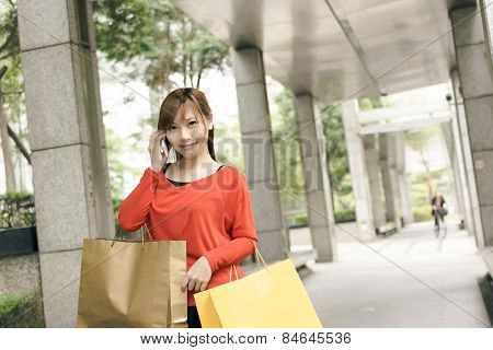 Smile shopping woman sit and use cellphone in Xinyi district, the business and commercial center in Taipei, Taiwan, Asia.