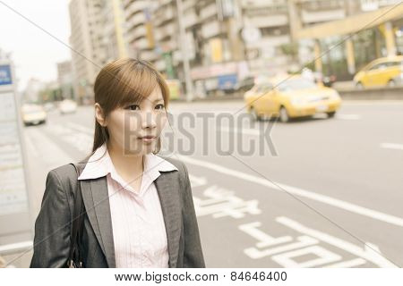 Asian young business woman wait the bus in the street, shot at Xinyi business district, Taipei, Taiwan.