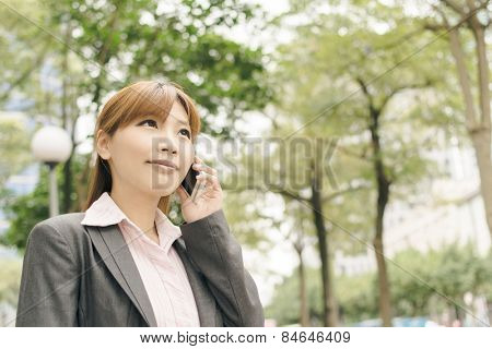 Attractive Asian business woman talk on phone under green tree in modern city, closeup portrait shot at Xinyi business district, Taipei, Taiwan.