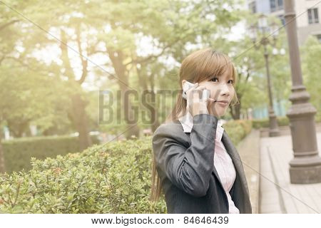 Asian business woman use cellphone in modern city, closeup portrait shot at Xinyi business district, Taipei, Taiwan.