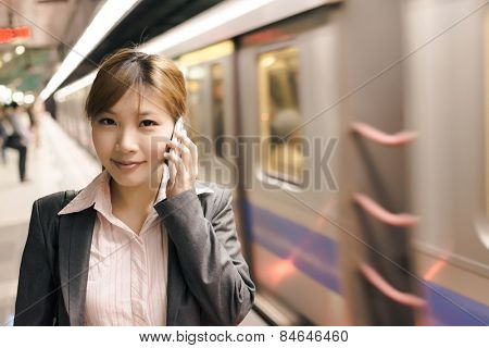 Asian young business woman use cellphone in the MRT station, shot at Xinyi business district, Taipei, Taiwan.