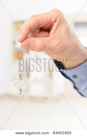 Hand with crystal pendulum, tool for dowsing.