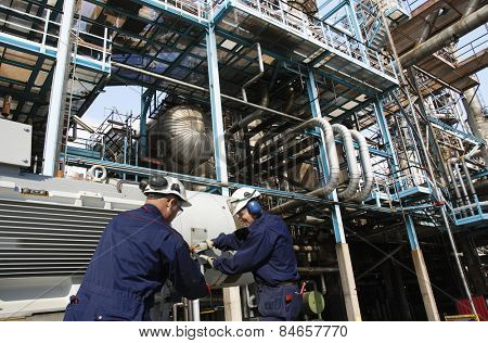 oil workers with machinery pumps inside large petroleum refinery