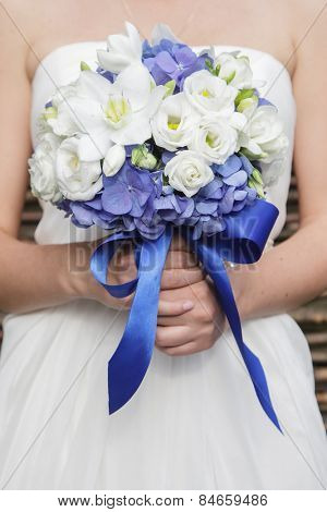 Beautiful wedding bouquet of hydrangea, eucharis and eustoma flowers in hands of the bride