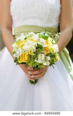 Beautiful wedding bouquet of roses, chrysanthemum and freesia flowers in hands of the bride