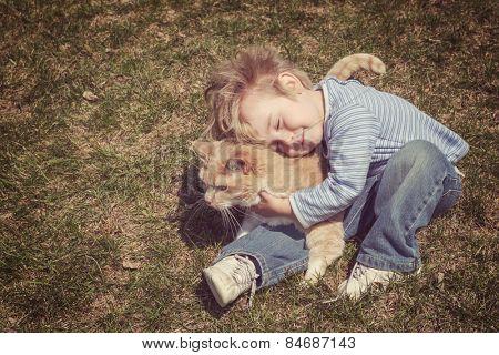 Young boy hugging his cat. Vintage instagram effect.