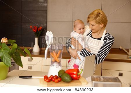 Young mother holding baby in arms, preparing baby food in the kitchen.