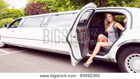 Beautiful blonde stepping out of limousine on a sunny day