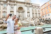 Tourist couple on travel taking selfie photo by Trevi Fountain in Rome, Italy. Happy young romantic couple traveling in Europe taking self-portrait with smartphone camera. Man and woman happy together poster