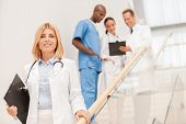 Confident female doctor moving downstairs and smiling while her colleagues talking in the background poster