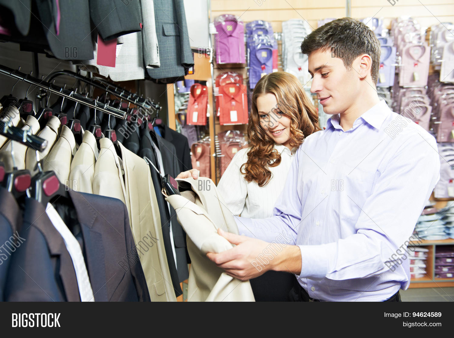 b308cfb1 Young man and woman choosing suit jacket during apparel shopping at clothing  store