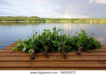 Traditional Finnish bath whisks made out of fresh birch leaves and twigs on a wet jetty by the lake on a Midsummer Eve. poster