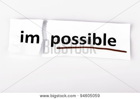 The word impossible changed to possible on torn paper and white background