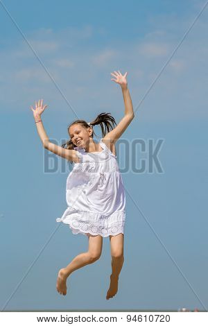 Girl In A White Sundress Jumps Over The Sea
