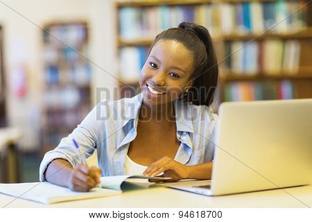 beautiful african college student studying a book in library