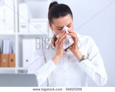 Young businesswoman blowing her nose, sits at her desk .