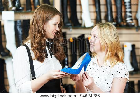 Young woman and seller assistant choosing footwear during shopping at shoe shop