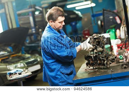 automotive mechanic worker works with engine or gearbox during automobile car maintenance at  repair service station