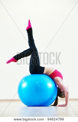 female instructor at stretching pilates exercises with finess ball in sport club