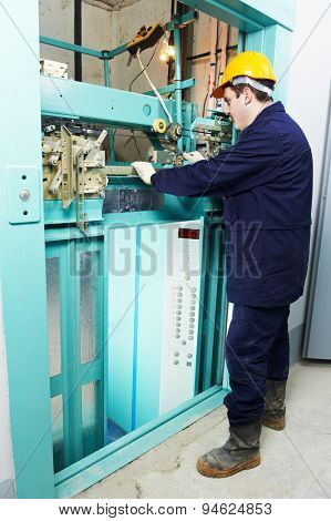 male technician machinist worker adjusting elevator mechanism of lift with spanner poster