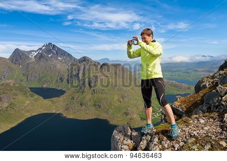 Sporty woman on the top of a mount Holandsmelen making photo Lofoten Norway