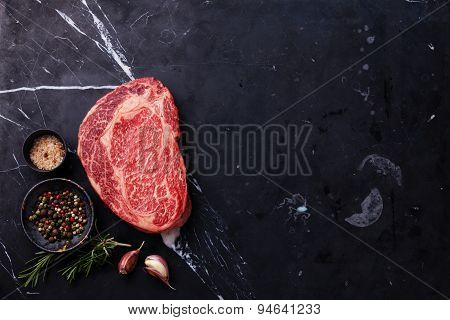 Raw Fresh Marbled Meat Black Angus Steak Ribeye And Seasonings On Dark Marble Background