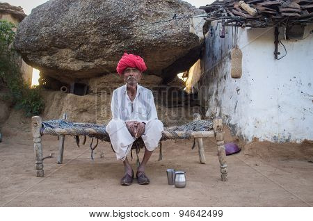 GODWAR REGION, INDIA - 13 FEBRUARY 2015: Elderly Rabari tribesman sits on bed in courtyard of home. Rabari or Rewari are an Indian community in the state of Gujarat.