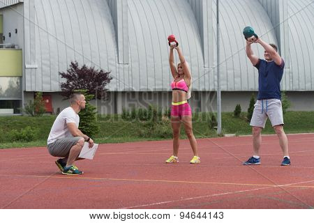 Group Of Young People Doing A Kettle Bell Exercise Outdoor With Instructor poster