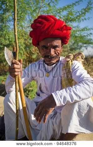 GODWAR REGION, INDIA - 14 FEBRUARY 2015: Elderly Rabari tribesman with red turban sits and holds axe and stick. Rabari or Rewari are an Indian community in the state of Gujarat.