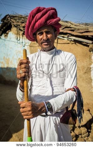 GODWAR REGION, INDIA - 13 FEBRUARY 2015: Rabari tribesman stands in courtyard in traditional clothes and holds herding stick. Rabari or Rewari are an Indian community in the state of Gujarat.