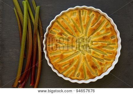 Rhubarb Cake With Stems In White Backing Tray On Slate Background