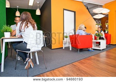 Lobby and multi-purpose waiting area, with several groups of people sitting at tables during informal meetings of a modern styled office