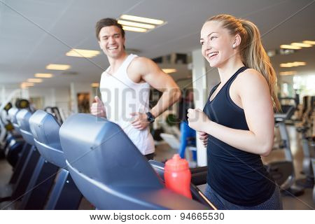 Happy Young Couple Running On Treadmill Device