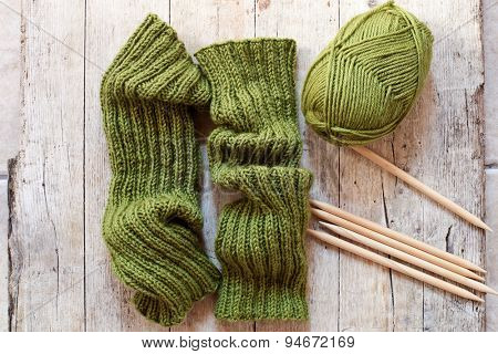 wool green legwarmers, knitting needles and yarn on wooden background