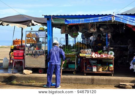 Con Dao, Vietnam - July 2, 2012: A Man Is Sweeping In Front Of His Food Street Vendor On The Con Dao