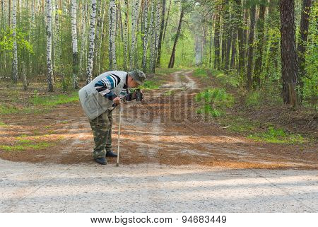 Senior photographer making photo with old film camera