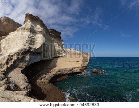 Ocean view - cliff, stones, blue sky, sea and stony shore