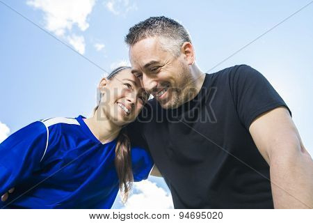 teenager girl with her father play soccer in a beautiful day