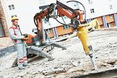 builder worker in safety protective equipment operating construction demolition machine robot. Focus on tool poster