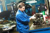 automotive mechanic worker works with engine or gearbox during automobile car maintenance at  repair service station poster