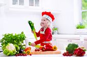 Kids cooking fresh vegetable salad in white kitchen. Children cook vegetables for vegetarian lunch. Toddler in chef hat eats healthy dinner. Little girl preparing and eating raw meal. Child nutrition. poster