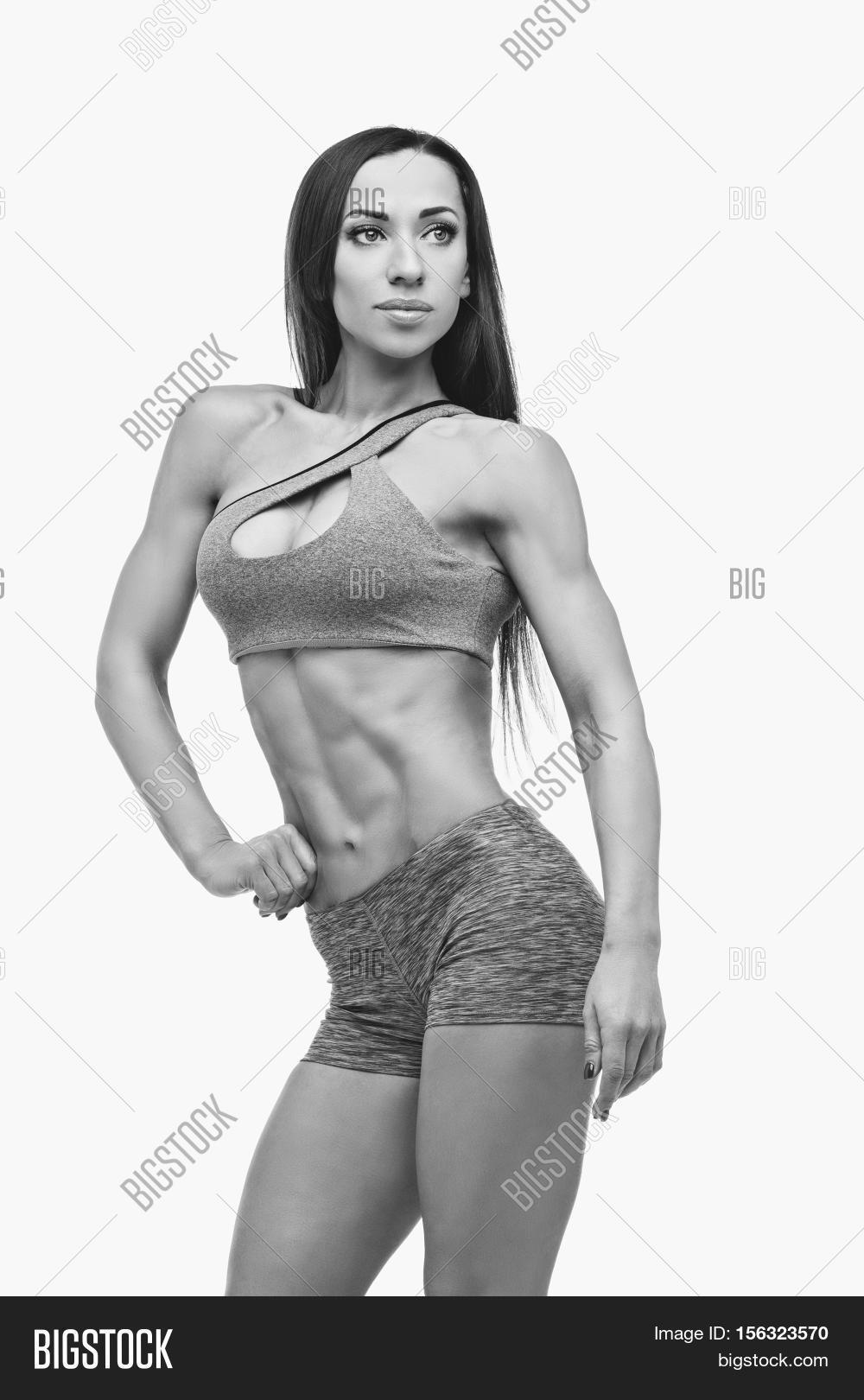f147a3e0b8 Beautiful fit muscular young woman in sport bra and shorts isolated on  white background. Perfect