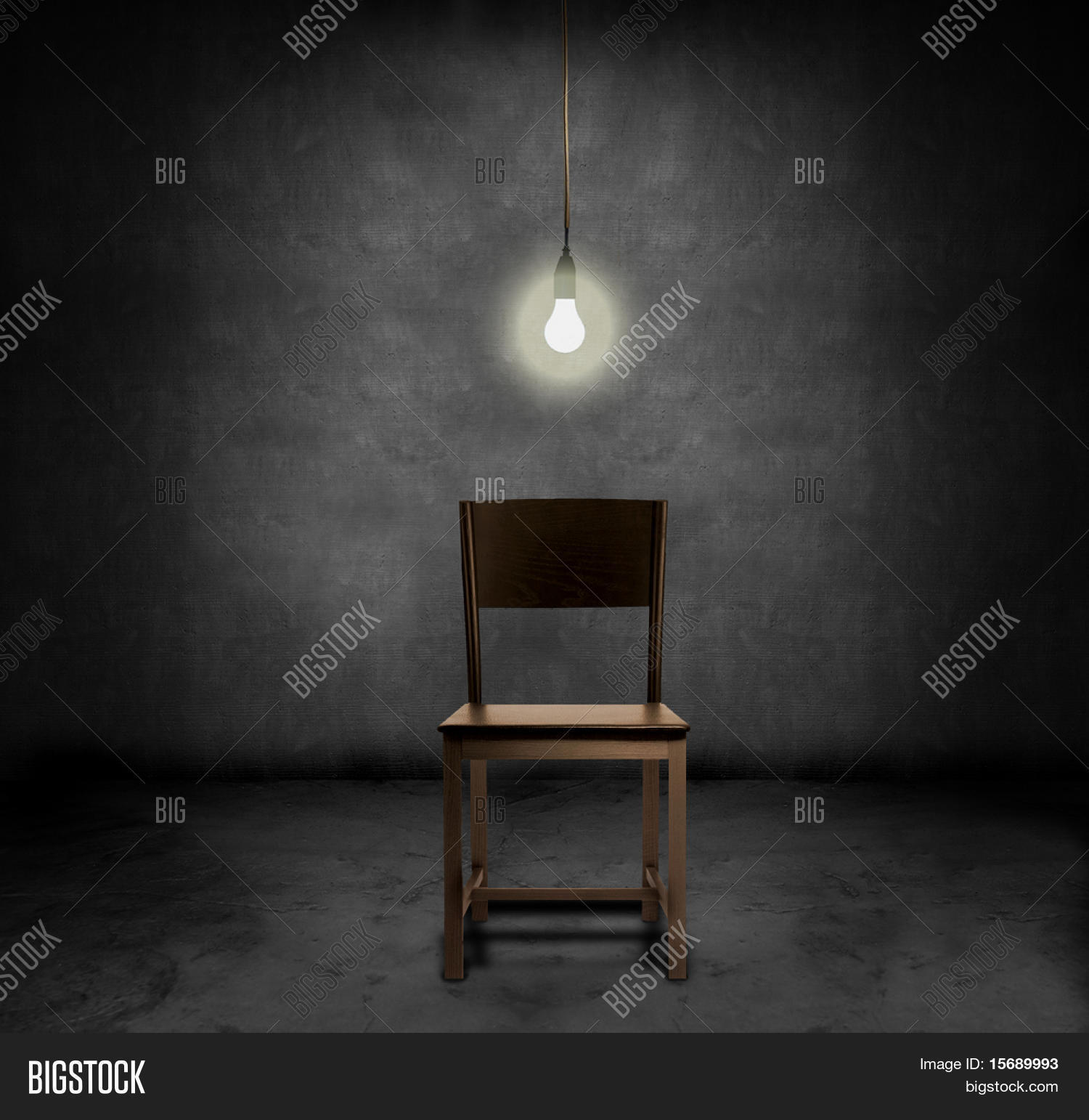 An Empty Chair And Hanging Light Bulb In A Dark Room