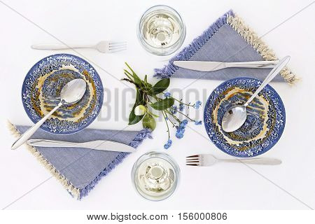 Empty plates after soup. Romantic dinner for two with white wine. Homey atmosphere clean white table. Top view