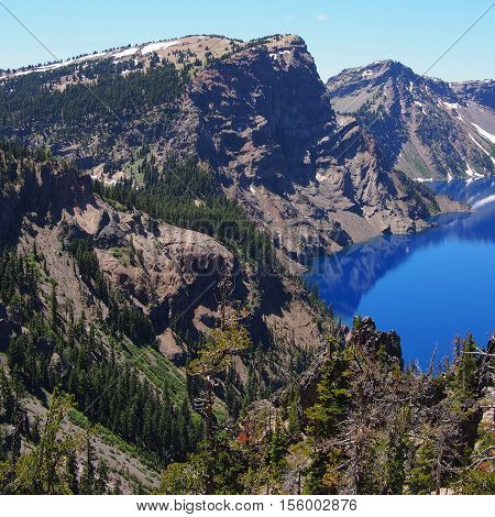 The jagged cliffs of Crater Lake reflect in the deep blue water.