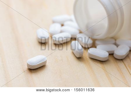 Oral medicine paracetamol white pills on wood table
