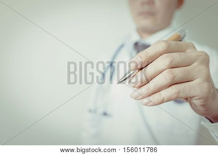 Detail of a doctor holding a pen vintage tone. Doctor man. Doctor woman. Pen in hand doctor. Doctor room. Clinic doctor.