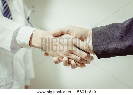 doctor and her lawyer shaking hands vintage tone.doctor's hands holding patient's hand for encouragement and empathy black and white. Doctor man. Doctor woman. Doctor hand. Doctor shake.