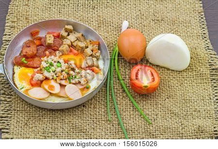 Indochina pan-fried egg with garnish (tomatoes chili pepper chili sauce bacon pork onion ) in sack fabric on black wooden
